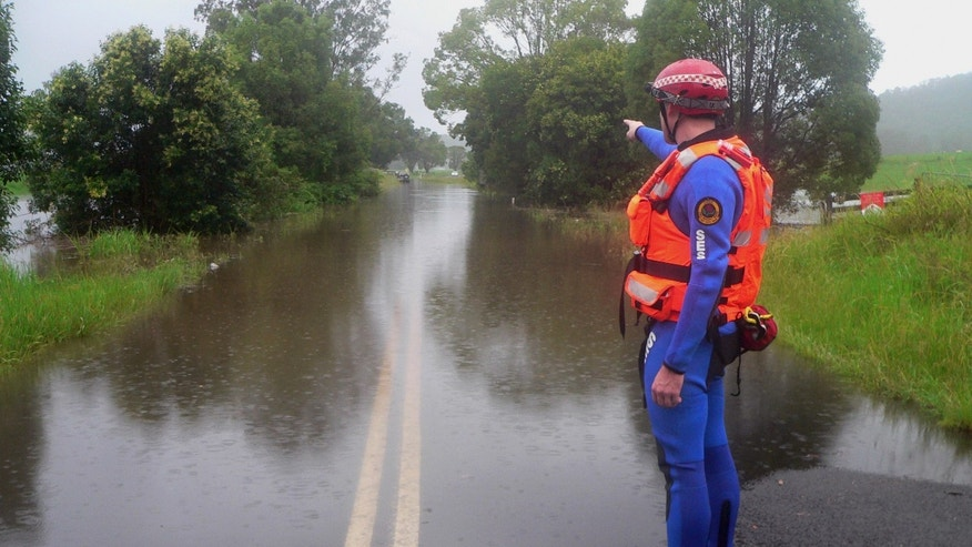 In this photo supplied by NSW State Emergency Service, a police officer gestures on Bruxner Highway, covered with floodwaters caused by torrential rains, in Lismore, northern New South Wales, Australia Tuesday, Jan. 29, 2013. Thousands of Australians huddled in shelters Tuesday as torrential rains flooded cities and towns in the northeast. With floodwaters expected to peak in most of the worst-hit areas later Tuesday, officials were rushing to move those in the highest-risk areas to safety. (AP Photo/NSW State Emergency Service, Samantha Cantwell ) NO SALES