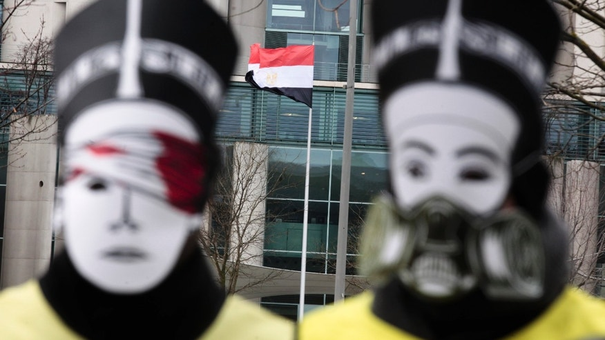 The Egypt flag waves in front of the chancellery photographed between activists of the human rights organization Amnesty International with Nefertiti masks protesting against the visit of Egyptian President Mohammed Morsi prior to a meeting of him with German Chancellor Angela Merkel in Berlin, Germany, Wednesday, Jan. 30, 2013. (AP Photo/Markus Schreiber)