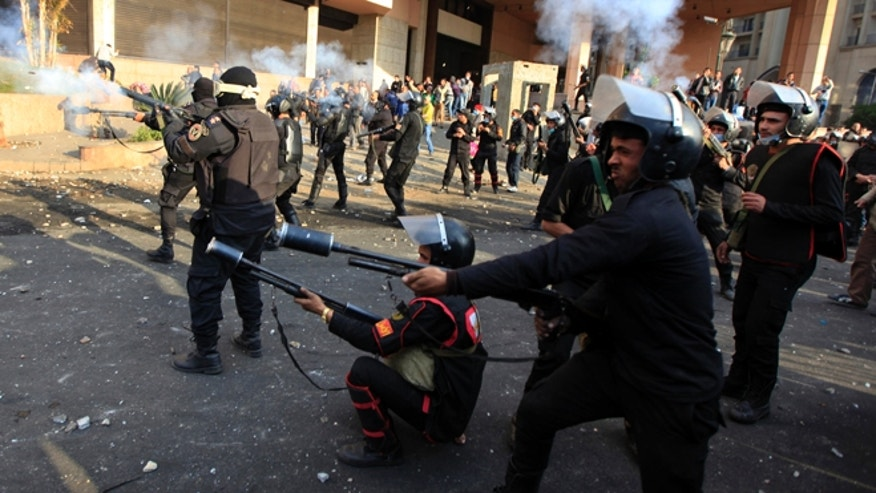 Jan. 29, 2013: Egyptian riot police fire tear gas at protesters, not seen, during clashes in front of the Semiramis Intercontinental hotel, background near Tahrir Square, Cairo, Egypt.