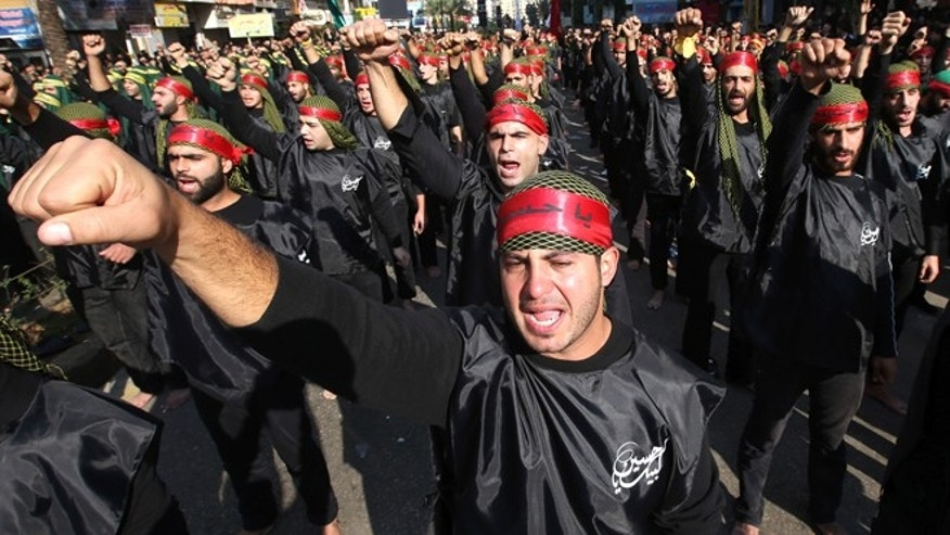 FILE -- Nov. 25, 2012: Shiite Muslim supporters of the Hezbollah, raise their fists as they chant slogans in support of pro-Hezbollah leader Sheik Hassan Nasrallah during a march to mark Ashoura Day, in the southern suburb of Beirut, Lebanon.
