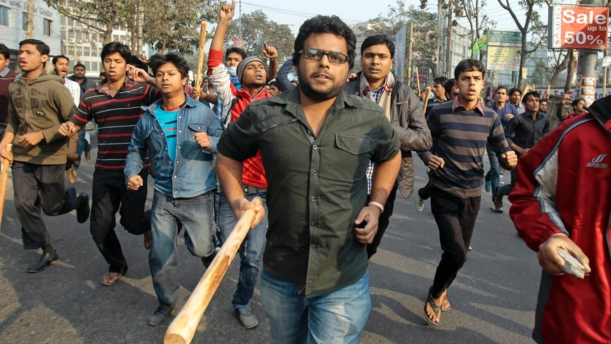 Jamaat-e-Islami activists armed with sticks march on a street in Dhaka, Bangladesh, Wednesday, Jan. 30, 2013. Hundreds of supporters of Bangladesh's main Islamist party attacked police Monday in a busy commercial district in the nation's capital, injuring many including at least eight security officers, an official said. The party has been demanding a halt to the trials of its top leaders facing charges of crimes against humanity involving the nation's 1971 independence war against Pakistan. (AP Photo/A.M. Ahad)
