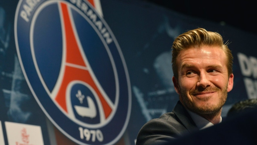 British soccer player David Backham, smiles during a press conference at the Parc des Princes stadium in Paris, Thursday, Jan. 31, 2013. David Beckham will join Paris Saint-Germain on Thursday, opting for a move to France after mulling over lucrative offers from around the world since leaving the Los Angeles Galaxy.(AP Photo/Benjamin Girette)