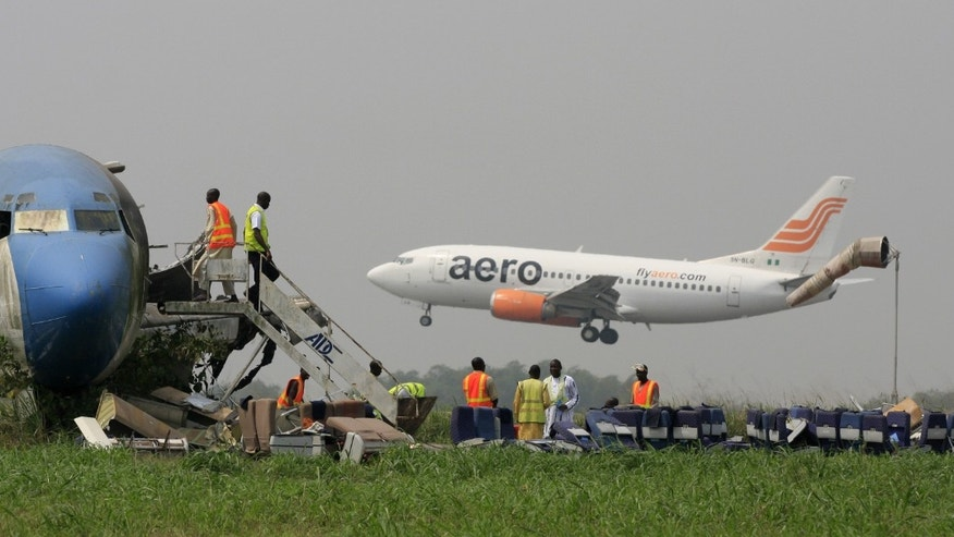 Jan. 31, 2013: A passenger plane lands as workers dismantle an abandoned aircraft at Murtala Muhammed International Airport in Lagos, Nigeria.