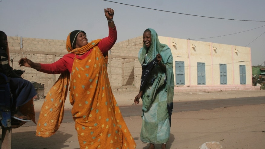 Jan. 31, 2013 - Women dance openly as they walk along a street in Timbuktu, Mali.