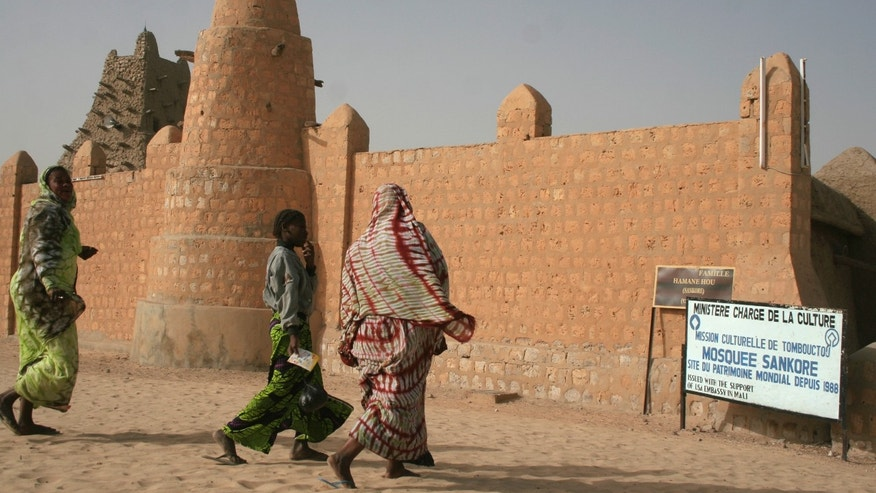 People dressed in colorful dress walk near the Sankore Mosque, a United Nations world heritage cultural site, which would not be allowed under the rule of Islamic militants who ruled the city until French troops took control, in Timbuktu, Mali, Thursday Jan. 31, 2013.  Many things have changed in Timbuktu since French troops parachuted in several days ago to take control of the area from Islamic militants, and now there is a growing sense of freedom. (AP Photo/Harouna Traore)