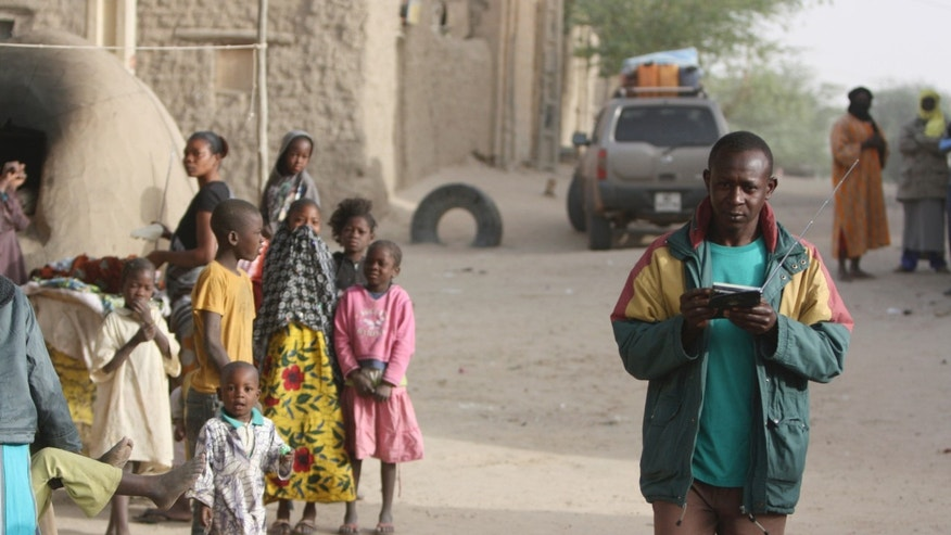 A man walks openly while holding a radio and watched by others, in a street in Timbuktu, Thursday Jan. 31, 2013. Many things have changed in Timbuktu since the Islamic militants ceased to enforce their law and relinquished power to French special forces who parachuted in several days ago and liberated this storied city, and now there is a growing sense of freedom. (AP Photo/Harouna Traore)