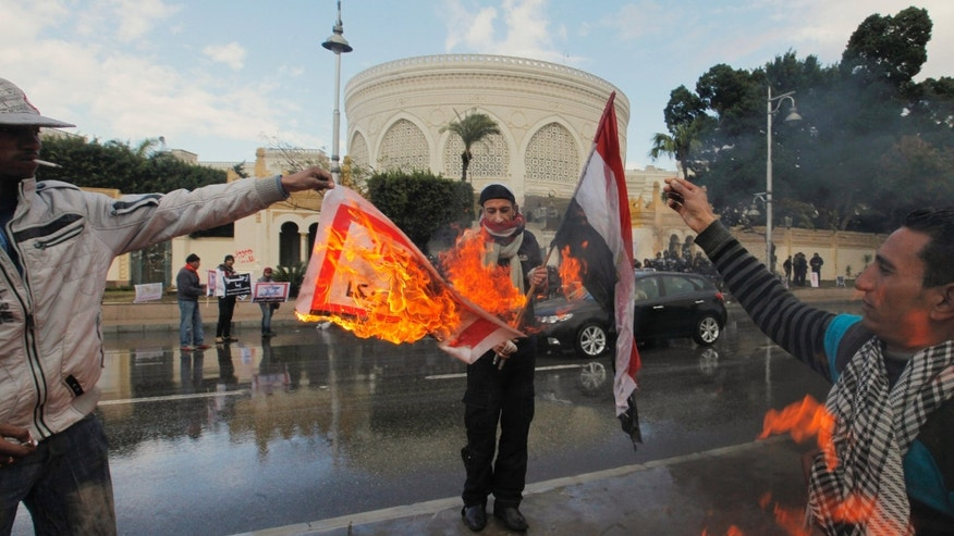 "Feb. 1, 2013 - Egyptian protesters burn an Arabic banner reading ""Hamas, brotherhood, Qatar and America, are Egyptian enemies,"" in front of the presidential palace in Cairo, Egypt."