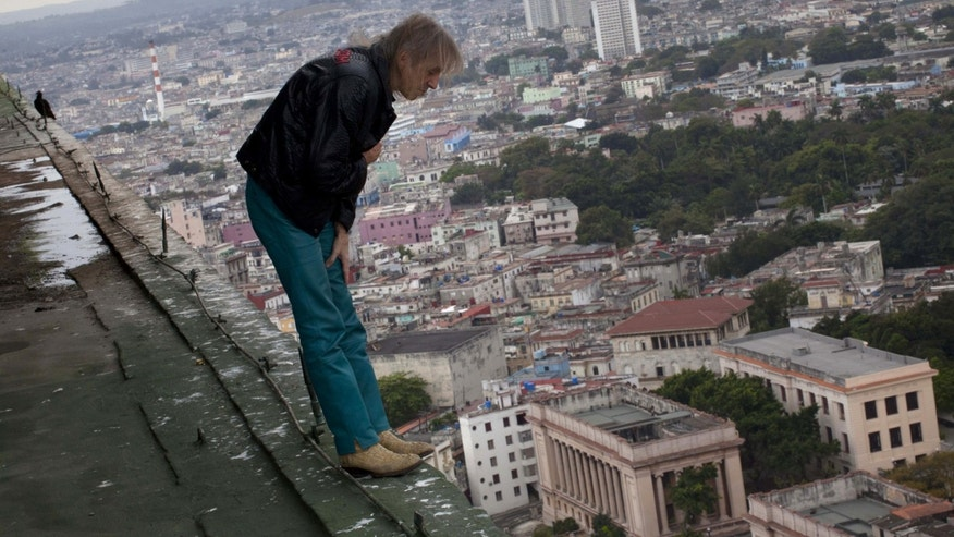 "Alain Robert known as ""Spiderman,"" looks over the edge from the roof of the Habana Libre hotel in Havana, Cuba, Friday, Feb. 1, 2013. Robert, from France, plans to climb the 27 floor hotel on Monday. (AP Photo/Ramon Espinosa)"