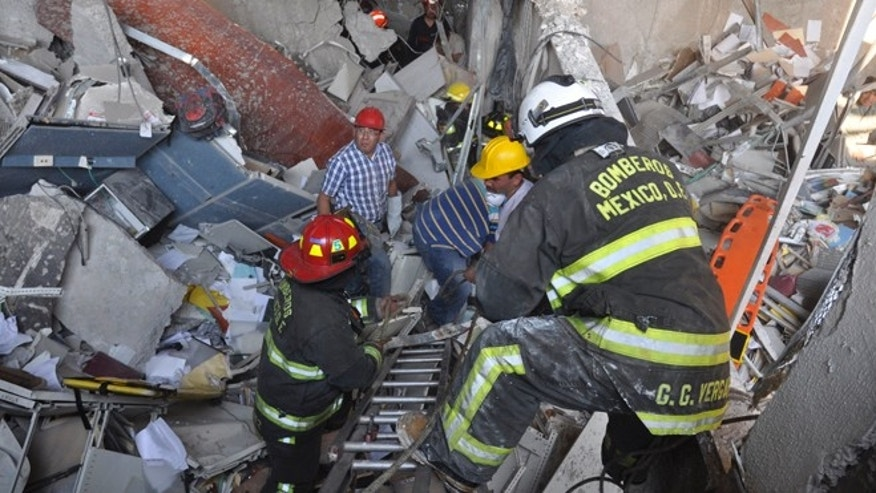 Jan. 31, 2013: Firefighters belonging to the Tacubaya sector and workers dig for survivors after an explosion at an adjacent building to the executive tower of Mexico's state-owned oil company PEMEX, in Mexico City.