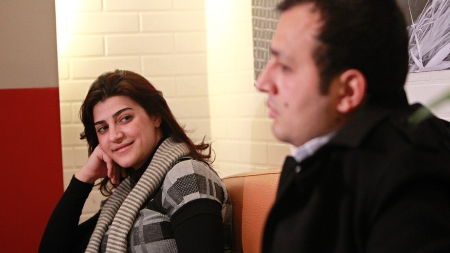 In this picture taken on Wednesday January 30, 2013, Lebanese couple Kholoud Sukkarieh, left, looks to her husband Nidal Darwish, right, during an interview with the Associated Press, in Beirut, Lebanon. She was an English language tutor with an easy smile and an independent streak. He was a gym receptionist who wanted to better himself. They met for English lessons, swapped views on life and fell in love. Three months ago, a notary married them before their friends and family _ but not in the eyes of the Lebanese government. The would-be marriage of Kholoud Sukkarieh and Nidal Darwish _ which the government has not recognized because a religious official did not register it _ has sparked a fierce debate in Lebanon over civil marriage and how its legalization would affect the country's tenuous sectarian system. (AP Photo/Bilal Hussein)