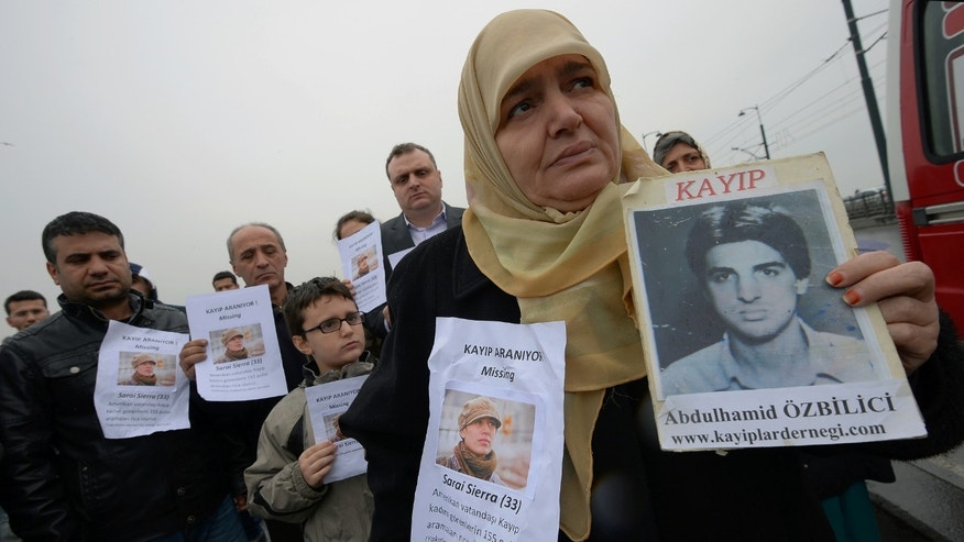 A Turkish mother shows a picture of her missing son as the members of the Istanbul-based Association For Families With Lost Relatives hand out flyers with photos of Sarai Sierra, a New York City woman who was found dead in Istanbul. (AP Photo)