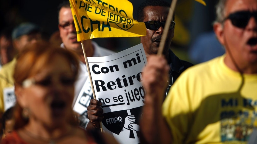 """A retiree carries a sign that reads in Spanish """"Do not play with my pension"""" during a protest outside the government pension headquarters in San Juan, Puerto Rico, Wednesday, Jan. 30, 2013. Puerto Rico is confronting what economists and financial analysts say is a ticking fiscal time bomb: A public pension system with a $37.3 billion unfunded liability that must be addressed soon, at a time when the U.S. island territory's government has little money to spare, or thousands of retirees could start to see benefit cuts. (AP Photo/Ricardo Arduengo)"""