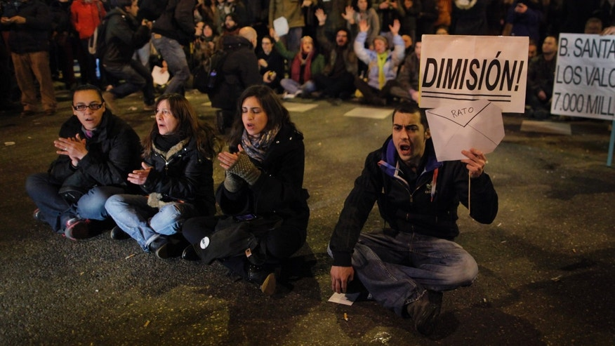 "Protestors shouts slogans as they hold an banner reading 'resign' during a demonstration against corruption, in Madrid, Spain, Thursday, Jan. 31, 2013. Spain's governing Popular Party insists its financial accounts are totally legal and denies a newspaper report of regular under-the-table payments to leading members, including current Prime Minister Mariano Rajoy. The scandal first broke when after the National Court reported that former party treasurer Luis Barcenas amassed an unexplained euro 22 million ($30 million) in a Swiss bank account several years ago. In a statement Thursday Jan. 31, 2013, the party denied the existence of ""hidden accounts"" or ""the systematic payment to certain people of money other than their monthly wages. (AP Photo/Andres Kudacki)"
