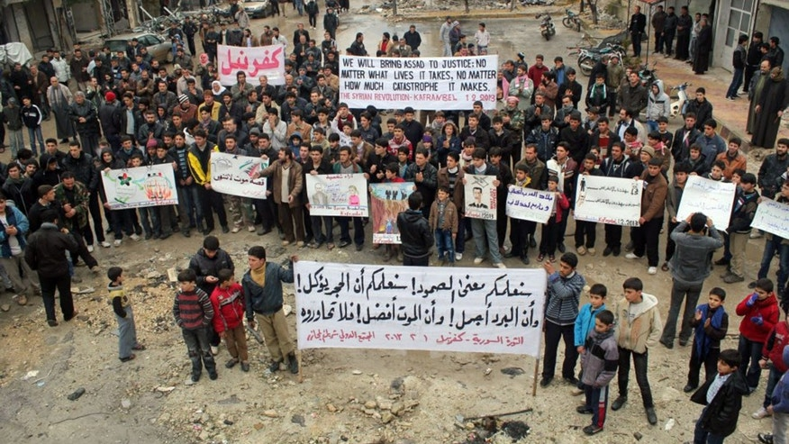 Feb. 1, 2013: This citizen journalism image provided by Edlib News Network, ENN, which has been authenticated based on its contents and other AP reporting, shows anti-Syrian regime protesters carrying banners during a demonstration, at Kafr Nabil town, in Idlib province, northern Syria.