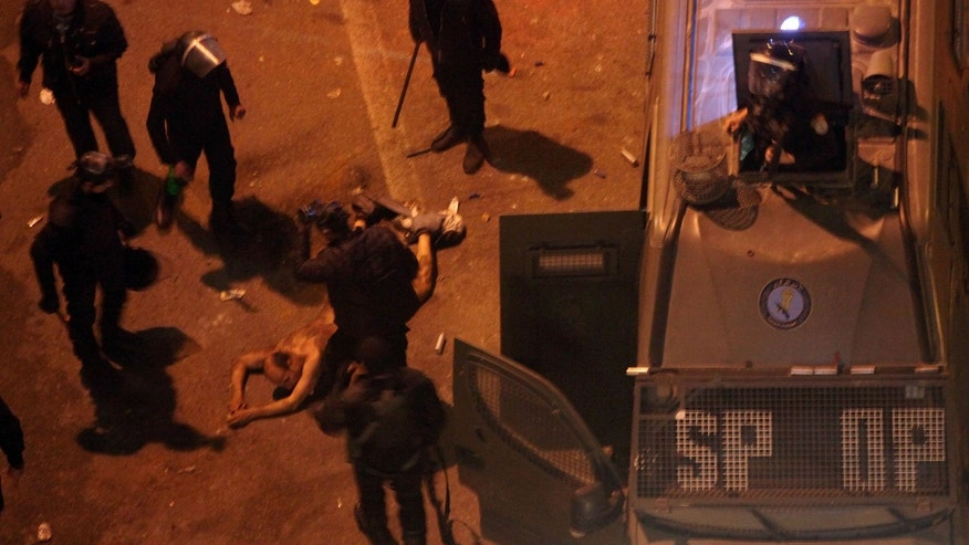 Feb. 1, 2013: Egyptian riot police beat a man, after stripping him, and before dragging him into a police van, during clashes next to the presidential palace in Cairo, Egypt.