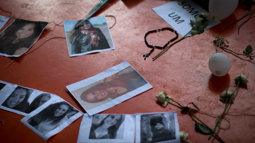 A makeshift memorial that include pictures of the victims of the Kiss nightclub fatal fire is seen inside the gymnasium where a collective funeral was held a day earlier, in Santa Maria, Brazil, Tuesday, Jan. 29, 2013. A fast-moving fire roared through the crowded, windowless nightclub, early Sunday, killing more than 230 people.  The first funeral services were held Monday for the victims. Most of the dead were college students 18 to 21 years old, but they also included some minors. Almost all died from smoke inhalation. (AP Photo/Felipe Dana)