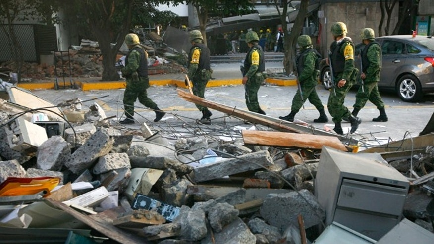 Feb. 1, 2013: Soldiers patrol next to debris caused by an explosion at the state-owned oil company PEMEX office complex in Mexico City.