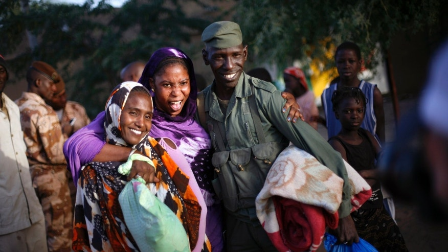 Malian women pose with a Malian soldier who just arrived in a convoy at the military base in Timbuktu, Mali, Saturday Feb. 2, 2013. French President Francois Hollande visited the fabled city for two hours, twenty days after the start of operation Serval. (AP Photo/Jerome Delay)