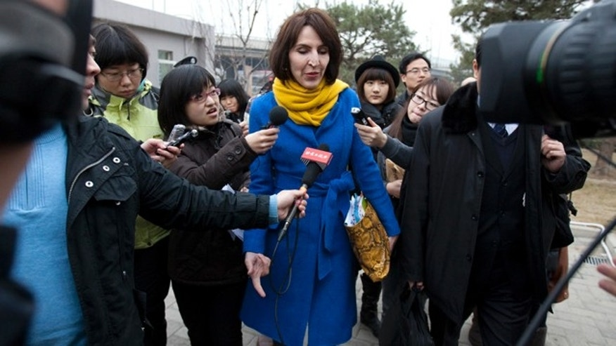 "March 22, 2012: Kim Lee, center, wife of ""Crazy English"" founder Li Yang, is surrounded by local journalists as she walks into a court for her divorce trial in Beijing, China."