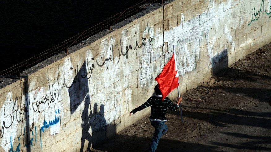 "In this Sunday, Feb. 3, 2013 photo, a Bahraini anti-government protester carries a national flag as he runs during a march in the western village of Malkiya, Bahrain. Graffiti on the wall refers to Bahrain's King Hamad bin Isa Al Khalifa, reading: ""Oh, Hamad, did you forget God's words?"" and goes into a verse from the Quran about injustice. (AP Photo/Hasan Jamali)"