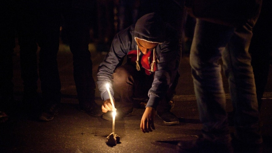 In this Saturday Feb. 2, 2013 photo, a demonstrator lights candles in memory of protester Mohammed Qorany at the spot where he died in clashes, near the presidential palace in Cairo, Egypt. Protesters and rights groups have accused police of using excessive force this past week during a wave of mass demonstrations in cities around the country called by opposition politicians, trying to wrest concessions from Morsi. (AP/Virginie Nguyen Hoang)