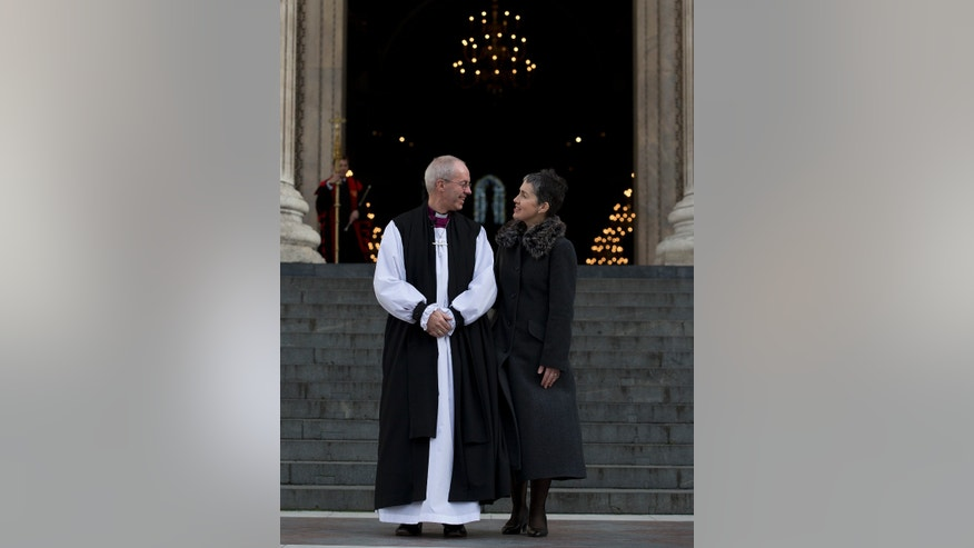 The new Archbishop of Canterbury, Justin Welby with his wife Caroline walks outside St Paul's Cathedral to pose for the media following his ceremony  known as the confIrmation of election in London, Monday, Feb. 4, 2013. (AP Photo/Alastair Grant)