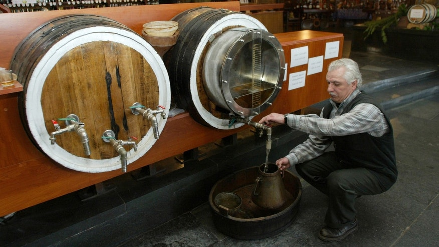 FILE - In this Thursday, April 6, 2006 file photo Georgian wine producer Givi Imerlishvili pours wine from a cask at his wine shop in Tbilisi, Georgia. Russia on Monday, Feb. 4, 2013, held talks on whether to resume Georgian wine imports after a seven-year ban, the first tentative step toward repairing the ruptured ties between the two ex-Soviet neighbors. Russia banned the imports of Georgian wine, mineral water, fruits and vegetables in 2006 amid rising political tensions in the run-up to a 2008 war.  (AP Photo/ Shakh  Aivazov, file)