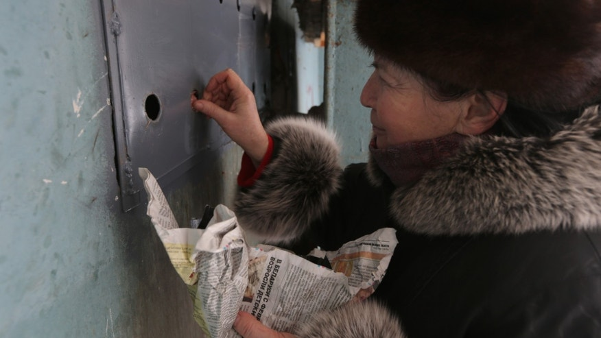Antonina Gayenko feeds cats through holes in an iron panel covering a basement window in the Belarusian capital Minsk, Monday, Feb. 4, 2013. Municipal authorities in Belarus are walling up stray cats in basements in compliance with Soviet-era regulations, dooming them to death of hunger. Belarus doesn't have shelters for stray animals. Municipal authorities said they wall up doors to basements in line with sanitary norms introduced in 1990, when Belarus was still part of the USSR. (AP Photo/Sergei Grits)