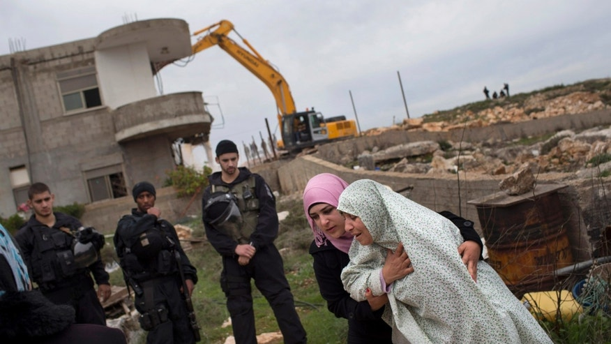 Palestinian woman cries while a bulldozer, background, demolishes her family house in the east Jerusalem neighborhood of Beit Hanina, Tuesday, Feb. 5, 2013. The municipality says the building was constructed without proper permits and that its structure was not sound. The 33-member family says it was waiting to receive permits.  (AP Photo/Bernat Armangue)