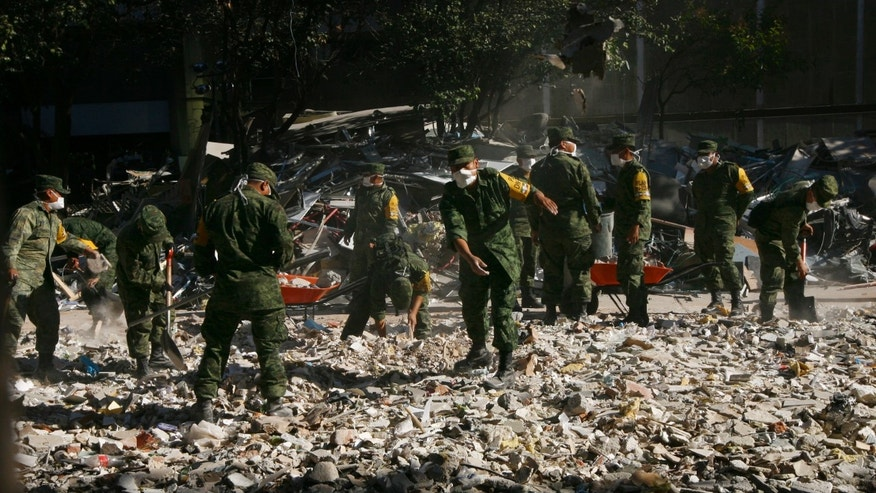 Feb. 3, 2013: Soldiers remove debris after an explosion at the state-owned oil company PEMEX office complex in Mexico City.