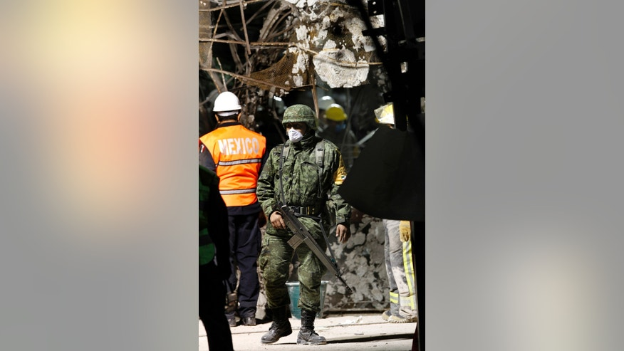 Feb. 3, 2013: A soldier patrols at the site where an explosion occurred at the state-owned oil company PEMEX office complex in Mexico City .