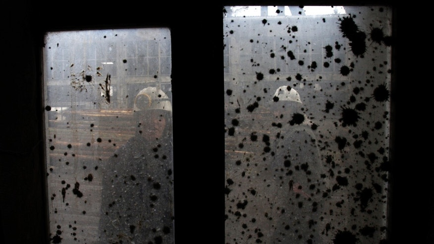 Woman coal miner Sakiba Colic, right, a Bosnian coal technologist, and one of her colleagues are seen through a smeared window outside the shaft of the coal mine in Breza, 20 kms north of Sarajevo, Bosnia on Wednesday, Jan. 16, 2013.  The mine in Breza is the only one in Bosnia where a group of women work deep underground in the coal mines alongside their male colleagues, a legacy of communism, but they're set to retire in three years, marking the end of an era for this community where almost everybody is connected to the coal mine. The shafts and elevators echo with laughter and tales of their grandchildren as women miners work alongside their male counterparts.(AP Photo/Amel Emric)