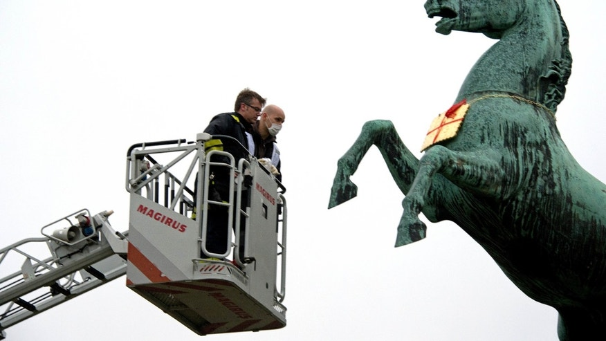 Feb. 5, 2013: A firefighter and a police officer look at a golden Leibniz cookie that hangs from a horses neck in front of the Leibniz University in Hannover, Germany.