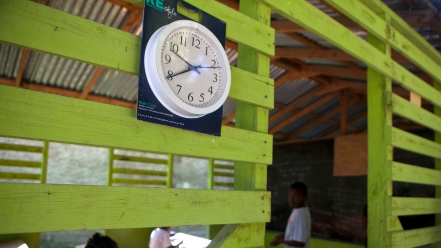 "In this Jan. 24, 2013 photo, a working clock still in its packaging hangs outside a classroom where students study the Creole language at the Louverture Cleary School, which also teaches French, English and Spanish, in Croix-des-Bouquets, Haiti. Haiti's first constitution, in 1805, declared that tuition would be free and attendance compulsory for primary students. But the quality of education lagged through the years, and plunged during the 29-year-long dynasty of Francois ""Papa Doc"" Duvalier and his son Jean-Claude, or ""Baby Doc."" Haiti's professionals fled into exile to escape political repression, spawning a major brain drain that country has never recovered from. (AP Photo/Dieu Nalio Chery)"