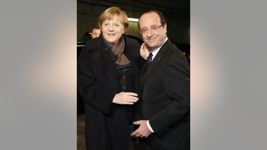 France's President Francois Hollande welcomes German Chancellor Angela Merkel at the Stade de France in Saint-Denis, near Paris, before attending a friendly international football match between France and Germany , Wednesday, Feb. 6, 2013. The match marks the 50th anniversary of the establishment of the Elysee Treaty, which paved the way for friendly relations between two countries that had previously endured a long and bitter rivalry. (AP Photo/Patrick Kovarik, Pool)