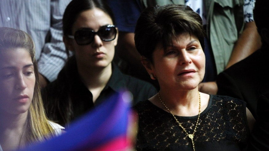 Raquel Marin, right, widow of former General Lino Oviedo, who was a presidential candidate with the UNACE party, attends her husband's wake at Congress where Oviedo's military hat sits on his coffin, front, in Asuncion, Paraguay, Wednesday, Feb. 6, 2013. The presidential hopeful died Saturday in a helicopter crash. Oviedo was returning with his bodyguard from a political rally in northern Paraguay Saturday night when his pilot encountered bad weather. All three were killed in the crash. The deadly crash ended a dramatic political career for Oviedo that included coups and several attempts to become the leader of this poor, grain-producing country. (AP Photo/Jorge Saenz)