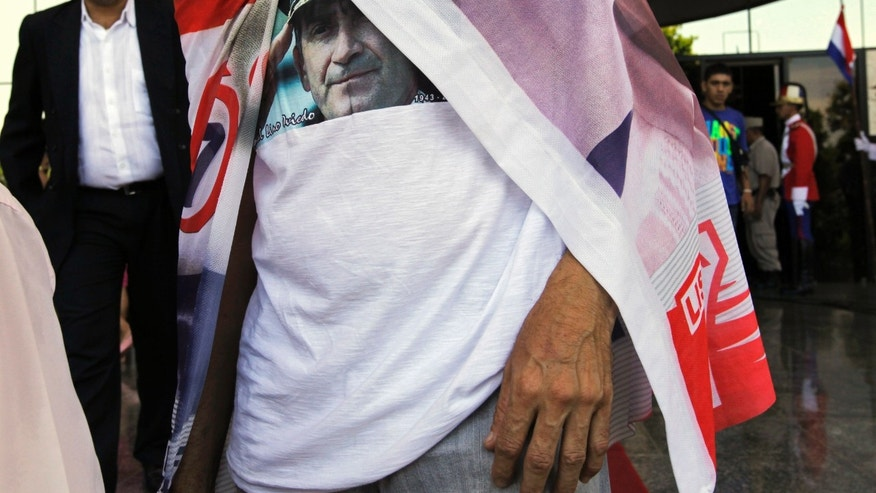 Wearing a T-shirt that shows an image of former Gen. Lino Oviedo, a supporter leaves Oviedo's memorial service at Congress in Asuncion, Paraguay, Wednesday, Feb. 6, 2013. A presidential candidate with the UNACE party, Oviedo died Saturday in a helicopter crash. He was returning with his bodyguard from a political rally in northern Paraguay Saturday night when his pilot encountered bad weather. All three were killed in the crash. The deadly crash ended a dramatic political career for Oviedo that included coups and several attempts to become the leader of this poor, grain-producing country. (AP Photo/Jorge Saenz) (AP Photo/Jorge Saenz) (AP Photo/Jorge Saenz)