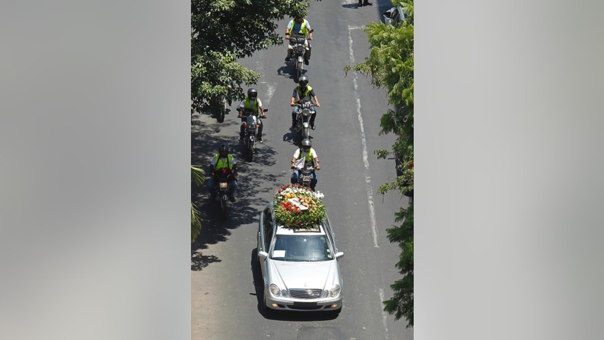 The flower covered hearse carrying the coffin of former General Lino Oviedo, who was a presidential candidate with the UNACE party, leaves Congress where a wake was held, to the UNACE party headquarters for another wake in Asuncion, Paraguay, Wednesday, Feb. 6, 2013. The presidential hopeful died Saturday in a helicopter crash. Oviedo was returning with his bodyguard from a political rally in northern Paraguay Saturday night when his pilot encountered bad weather. All three were killed in the crash. The deadly crash ended a dramatic political career for Oviedo that included coups and several attempts to become the leader of this poor, grain-producing country. (AP Photo/Jorge Saenz)