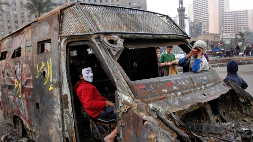 Egyptians play inside a captured state security armored vehicle that demonstrators commandeered during clashes with security forces and brought to Tahrir Square, the focal point of Egyptian uprising, in Cairo, Egypt, Tuesday, Feb. 5, 2013. More than 60 people have died in recent protests across Egypt that began on Jan. 24, 2013, the eve of the second anniversary of the start of the uprising that toppled autocrat Hosni Mubarak. (AP Photo/Amr Nabil)