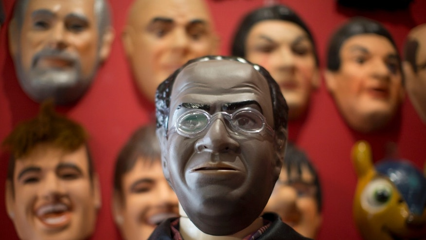 In this Jan. 21, 2013 photo, a Carnival mask in the likeness of Brazilian Supreme Court Justice Joaquim Barbosa is displayed on a mannequin at the Condal factory in Sao Goncalo, near Rio de Janeiro, Brazil. Condal is Brazil's oldest and most productive mask factory that is run by Olga Valles, a family business started in 1958. Barbosa, born into poverty, became the first black judge in the nation's top court when he took office in 2003. Barbosa went on to make a name for himself when he presided over a wide-ranging political corruption trial involving a cash-for-votes scheme. Now, average Brazilians are honoring him during Carnival by buying his mask in droves, said Valles. Brazil's annual five-day extravaganza begins Friday. (AP Photo/Felipe Dana)