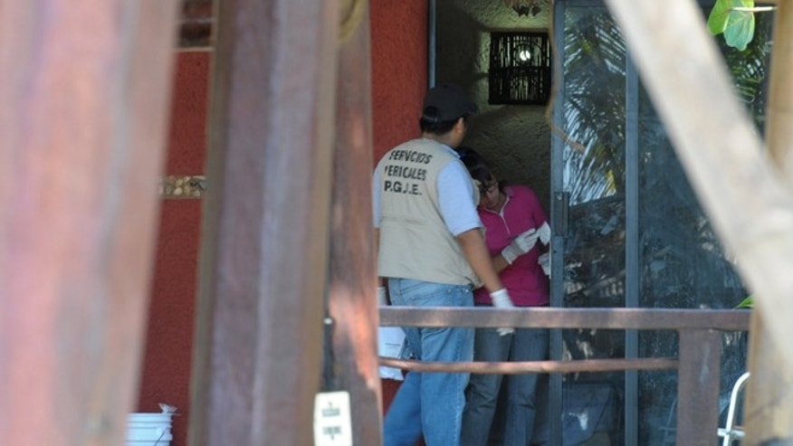 Police investigators work to obtain fingerprints on a door at the home where masked, armed men broke in, in Acapulco, Mexico, Tuesday Feb. 5, 2013. According to the mayor of Acapulco, five masked men burst into this house that Spanish tourists had rented on the outskirts of Acapulco, in a low-key area near the beach, and held a group of six Spanish men and one Mexican woman at gunpoint, while they raped the six Spanish women before dawn on Monday. (AP Photo/Bernandino Hernandez)