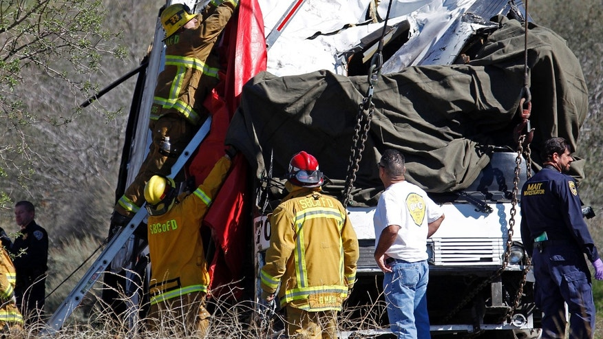 San Bernardino County firefighters hang a drape over the smashed front of a tour bus where at least eight people were killed after it collided with tow other vehicles just north of Yucaipa, Calif., Sunday, Feb. 3, 2013. The bus was carying a group from Tijuana, Mexico.