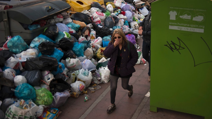 A woman covers her nose as she walks past rubbish bags piled up next to overflowing garbage containers during a rubbish collection strike in Seville, Spain Thursday Feb. 7, 2013.  City authorities estimate there is some 7,000 tons of rubbish-filled bags lying about the ancient city. The 11-day-old strike is over wage cuts and working hours. (AP Photo/Laura Leon)