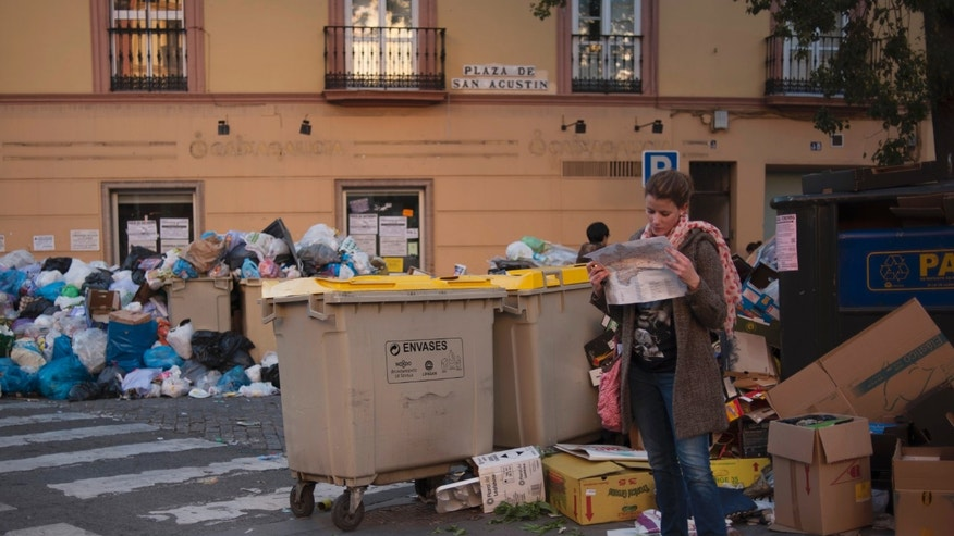 A woman looks at a map of Andalusia amid rubbish bags piled up next to overflowing garbage containers during a rubbish collection strike in Seville, Spain Thursday Feb. 7, 2013.  City authorities estimate there is some 7,000 tons of rubbish-filled bags lying about the ancient city. The 11-day-old strike is over wage cuts and working hours. (AP Photo/Laura Leon)