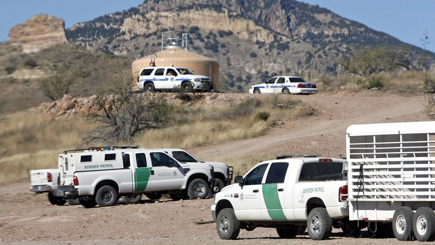 U.S. Border Patrol and Arizona Department of Public Safety vehicles crowd an area near Pena Blanca Lake in Coronado National Forest northwest of Nogales, Ariz., on Wednesday, Dec. 15, 2010, during a search for a suspect in an overnight shootout resulted in the death of a Border Patrol agent. (AP Photo/Arizona Daily Star, Greg Bryan)