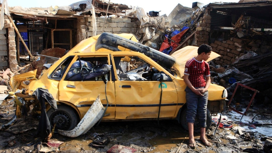 Feb. 8, 2013 - An Iraqi boy stands near a destroyed car at the scene of a car bomb attack in Baghdad's northern Kazimyah neighborhood.