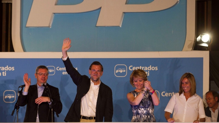 FILE - In this May 22, 2011 file photo, Spain's then conservative opposition leader Mariano Rajoy, second left, waves next to Madrid Mayor Alberto Ruiz Galladon, left, President of Madrid's regional government Esperanza Aguirre, third left, and Ana Mato, party spokesperson, on the balcony of the headquarters of the conservative Popular Party in Madrid, Spain after winning the general elections. After two years of recession, harsh austerity programs, sky-high unemployment and an unstable footing on the world's markets. Now comes a corruption scandal that has shaken the government to its core. And it's raising questions whether Prime Minister Mariano Rajoy can survive the fallout from allegations that he and others benefited from years of slush fund handouts. (AP Photo/Paul White, File)