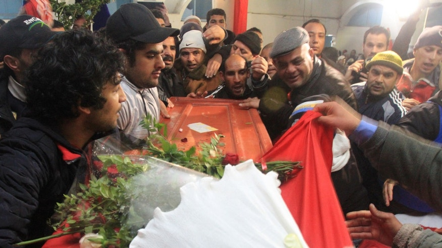 Feb. 8, 2013 - Relatives of slain opposition leader Chokri Belaid leave the house of his father while carrying the coffin prior to his funeral in Tunis, Friday.
