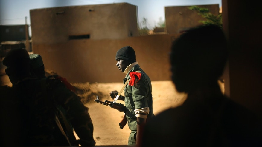 A Malian soldier walks in Gao, northern Mali, Thursday, Feb. 7, 2013. French troops began to withdraw from Timbuktu Thursday after securing the fabled city as they ramped up their mission in another northern Mali city, searching for Islamic extremists who may be mixing among the local population. (AP Photo/Jerome Delay)