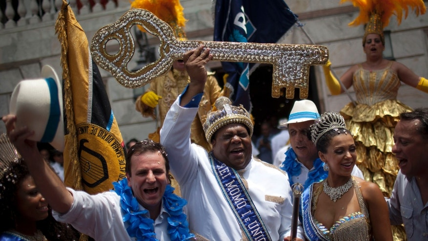 The mythical jester figure who reigns over Carnival, this year's King Momo; the crowned and costumed Milton Rodrigues Junior, center, holds up the key of the city that was given by Rio de Janeiro's Mayor Eduardo Paes, left, at the official ceremony kicking off the five-day bash, in Rio de Janeiro, Brazil, Friday, Feb. 8, 2013. (AP Photo/Felipe Dana)